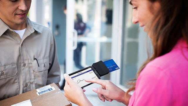 Woman signing for package using Square Reader on smart phone with her Visa card for payment.